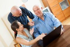 Советник   около зрелых пар с компьтер-книжкой Стоковое Фото