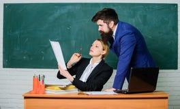 Советуйте с с коллегой Помогите мне с документами Учитель и инспектор работая совместно в классе школы воспитательно стоковые фото