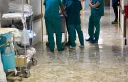 Советуйте с среди хирургов и медсестер в коридорах больницы среди группы Стоковое Изображение