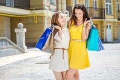 Совместная прогулка 2 подруги держа хозяйственные сумки и aroun прогулки Стоковые Изображения