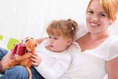 Совместно: дочь сидя на подоле матери при изолированный настоящий момент Стоковые Фото