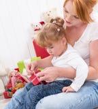 Совместно: дочь сидя на подоле матери при изолированный настоящий момент Стоковые Изображения RF