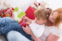 Совместно: дочь сидя на подоле матери при изолированный настоящий момент Стоковое Изображение RF
