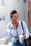 Современная африканская женщина разговаривая и идя с мобильным телефоном стоковая фотография rf