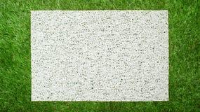 Современная белая циновка на предпосылке зеленой травы Стоковые Изображения