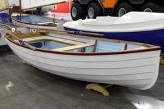 Современная белая шлюпка при весла уложенные вдоль стороны Стоковые Изображения