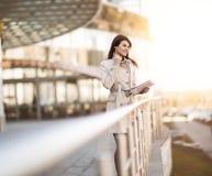 Современная бизнес-леди работая на цифровой таблетке, стоя рядом с офисным зданием Стоковые Изображения RF