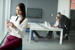 Современная бизнес-леди используя мобильный телефон пока бизнесмены Стоковое Изображение
