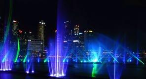 Современная выставка фонтана голубого зеленого цвета на море и абстрактных архитектурах и горизонт ночи в Сингапуре стоковые фото