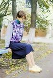 Современная девушка задумчиво сидит на стенде в улице стоковые изображения rf