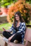 Современная девушка подростка используя умный телефон в парке над зеленой предпосылкой Стоковые Изображения RF