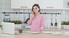 Современная женщина в кухне, связывая на телефоне с клиентами акции видеоматериалы