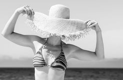 Современная женщина на seashore пряча за соломенной шляпой пляжа стоковое изображение