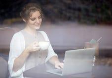 Современная женщина работая на компьтер-книжке в кофейне Снятый через ветер Стоковые Изображения RF