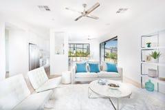 Современная живущая комната при белые стены загоренные с солнечным светом Стоковое фото RF