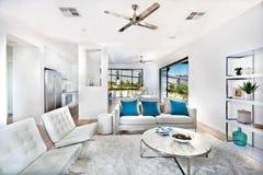 Современная живущая комната при белые стены загоренные с солнечным светом Стоковые Фото
