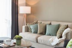 современная живущая комната с зелеными подушками на уютной софе и деревянном Ла Стоковые Изображения RF