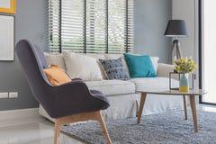 Современная живущая комната с современными стулом и софой стоковые изображения