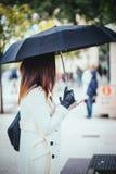 Современная и элегантная женщина с зонтиком на городе, используя чернь Стоковое фото RF