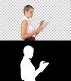 Современная коммерсантка используя планшет пока идущ, канал альфы стоковое изображение