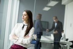 Современная коммерсантка стоя в современном офисе с молодым busine Стоковые Фото