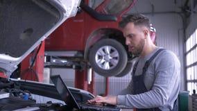 Современная компьютерная технология в ремонте автомобиля, профессиональный техник использует ноутбук для корабля диагностик с отк акции видеоматериалы