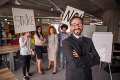 Современная концепция офиса, директор стоя с его задней частью к поразительным cowokers стоковое фото