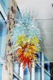 Современная красочная стеклянная люстра на белой стене Стоковые Фото