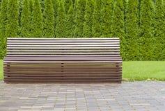 Современная кривая сформировала мебель коричневой деревянной скамьи внешнюю в парке как фоновое изображение Стоковые Фото