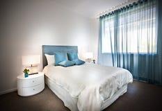 Современная кровать с белыми листами и голубыми подушками стоковые изображения rf