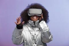 Современная курчавая коричнев-с волосами девушка одетая в цвета серебр куртке использует представления стекел виртуальной реально стоковое изображение