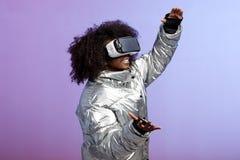 Современная курчавая коричнев-с волосами девушка одетая в цвета серебр куртке использует представления стекел виртуальной реально стоковое изображение rf