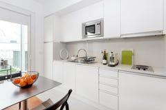 Современная кухня с белой мебелью стоковая фотография rf