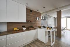 Современная кухня с белыми и коричневыми стенами стоковые фото