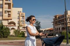 Современная мать на улице города нажимая pram (детская сидячая коляска) Стоковые Изображения RF