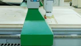 Современная машина woodworking в действии Режет курчавые части от листа переклейки Продукция деревянной мебели сток-видео