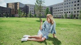 Современная молодая женщина в голубых джинсах одевает на зеленой траве со смартфоном акции видеоматериалы