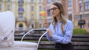 Современная молодая женщина в костюме офиса играя с newborn экипажом, держа трещотку видеоматериал