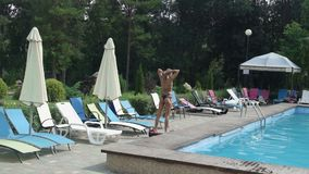 Современная молодая женщина идя с Hoverboard около голубого бассейна на солнечный день видеоматериал