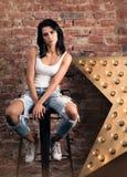 Современная молодая женщина представляя на стуле Стильное возникновение, белая футболка и джинсы с отверстиями Стоковые Фото