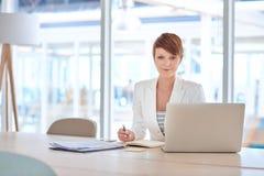 Современная молодая коммерсантка на ее столе в ярком офисе Стоковая Фотография