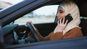Современная мусульманская женщина имея телефон говорит за рулем видеоматериал