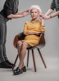 Современная пожилая женщина сидя на деревянном стуле в студии стоковое изображение
