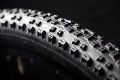 Современная покрышка горного велосипеда гонки MTB изолированная на черной предпосылке Стоковые Фотографии RF