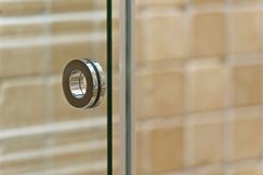 Современная ручка на стеклянной двери в bathroom стоковая фотография rf