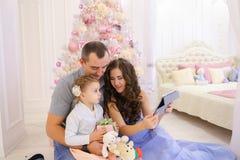 Современная семья разговаривает с родственниками на Skype в просторной спальне стоковые изображения rf