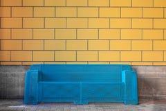 Современная софа медного штейна против мебели желтой стены плитки городской Стоковые Изображения RF