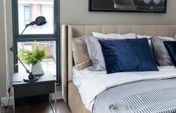 Современная спальня при включении голубые подушки и черная лампа таблица Стоковые Изображения RF