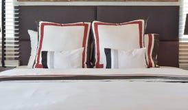 Современная спальня с белизной и striped подушки на кровати Стоковая Фотография RF