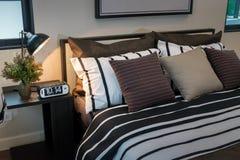 Современная спальня с коричневым цветом, черно-белые striped подушки Стоковая Фотография
